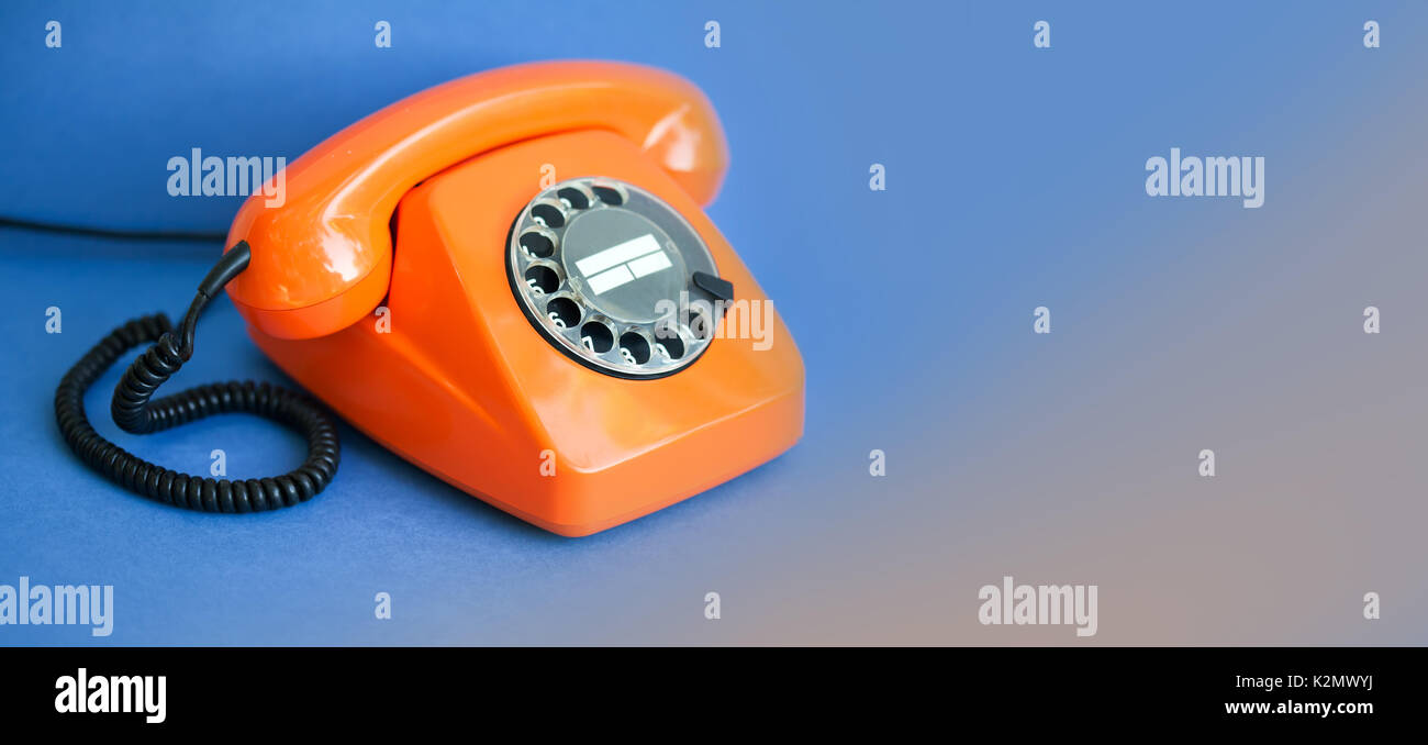 Orange phone blue background. Retro style plastic handset receiver communication call center concept. Shallow depth field. copy space template - Stock Image