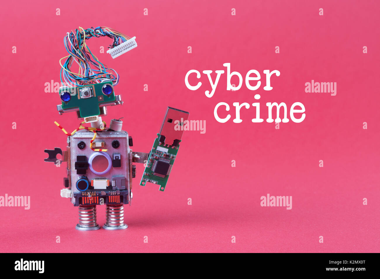 Cybercrime and data hacking concept. Retro robot with usb flash storage stick, stylish computer character blue eyed head, electrical wire hairstyle. Pink background - Stock Image