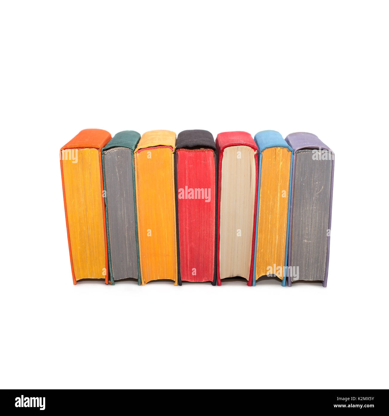 Stack of colorful books isolated on white background. Seven hardcover volumes. red black yellow pages. - Stock Image
