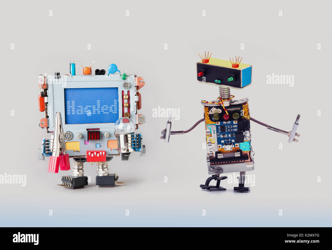 Cyber crime concept. IT specialist robot serviceman with screwdrivers looking at colorful computer. Alert warning message Hacked on blue display. Gray gradient background - Stock Image