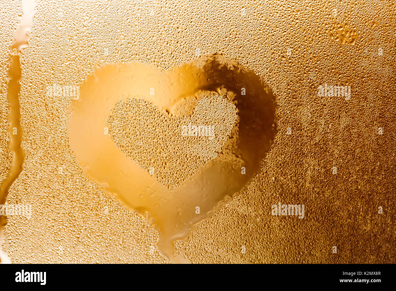 Love heart shape and raindrops textured pattern. Abstract golden color window with water droplet, liquid bubbles. macro view. Shallow depth of field. Valentines day concept. horizontal - Stock Image