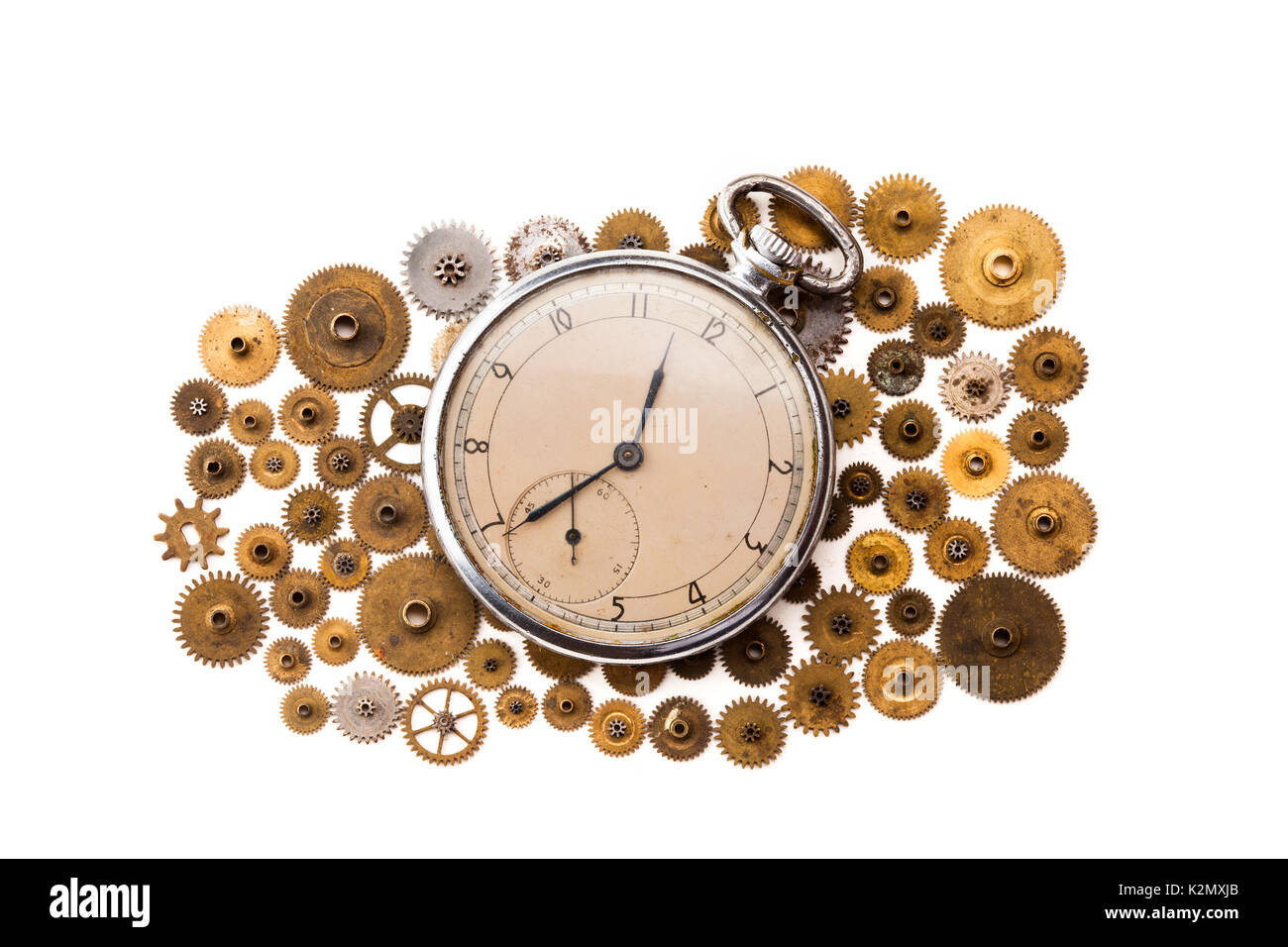 Vintage pocket watch and cogs gears wheels on white background. Vintage clockwork parts closeup. shallow depth of field. - Stock Image