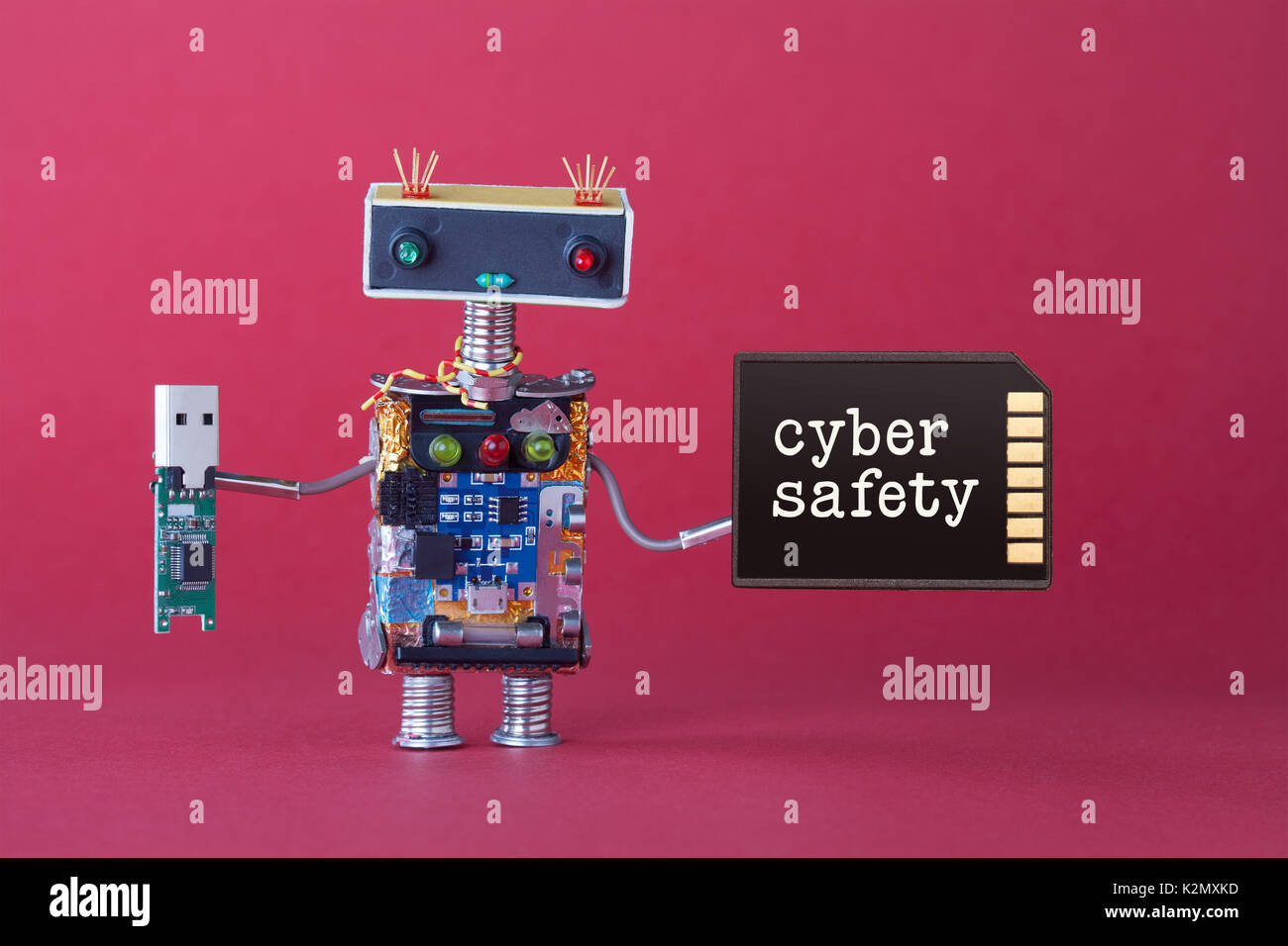 Cyber Safety Data Storage Concept. System Administrator Robot Toy With Usb  Flash Stick And Memory Card On Red Background. Copy Space Macro View Photo.