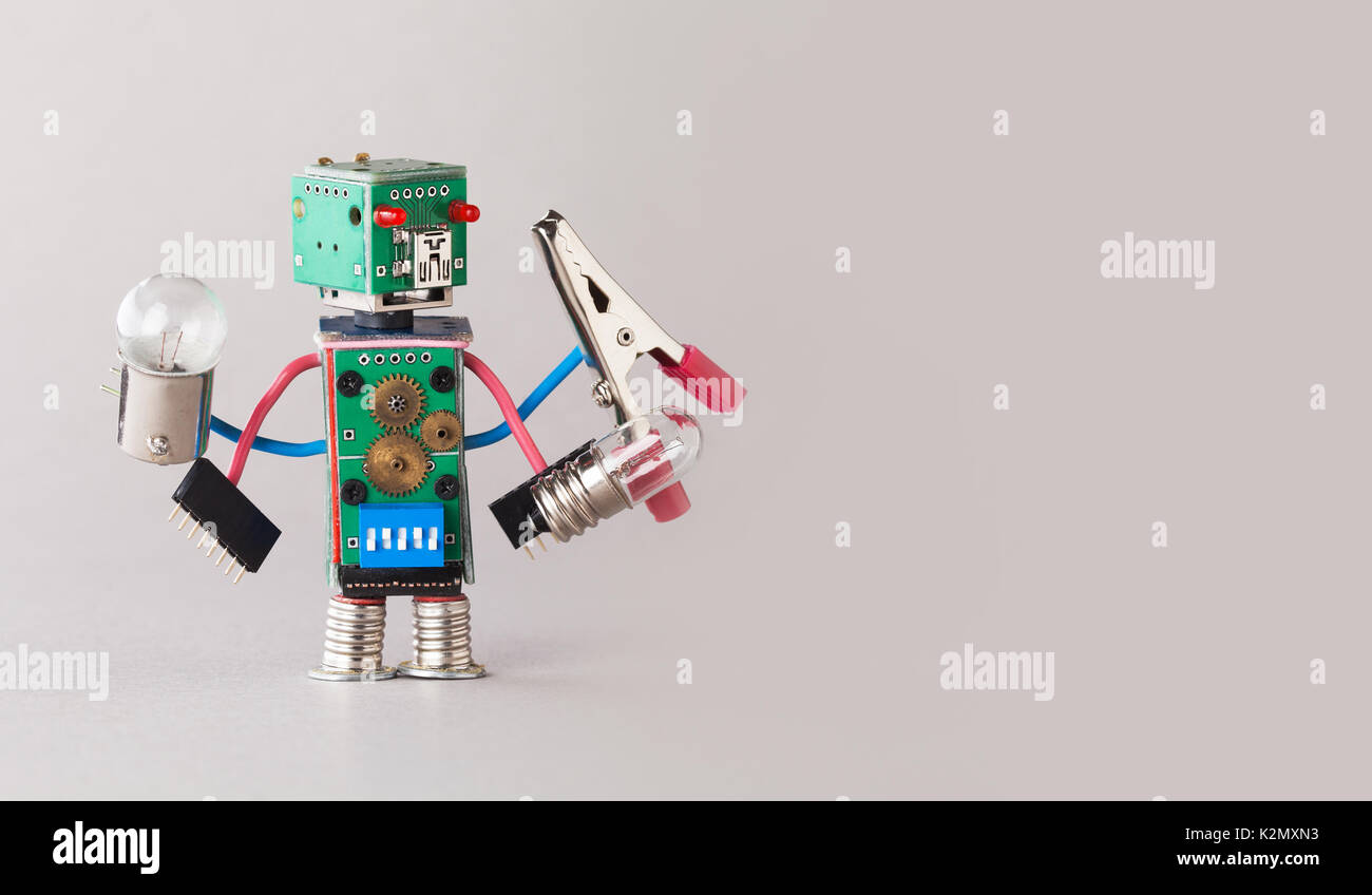 Multifunctional electrician robot with light bulbs and pliers in four hands. Colorful circuit board toy character holds different retro lamps. Funny electronic parts. copy space gray background. - Stock Image
