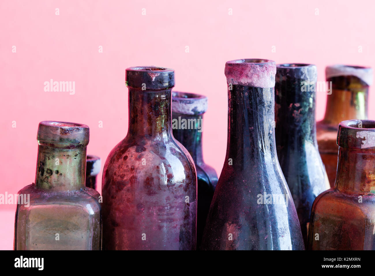 Retro design bottles macro view. Colorful dirty glass flacon set. Pink background, shallow depth of field - Stock Image