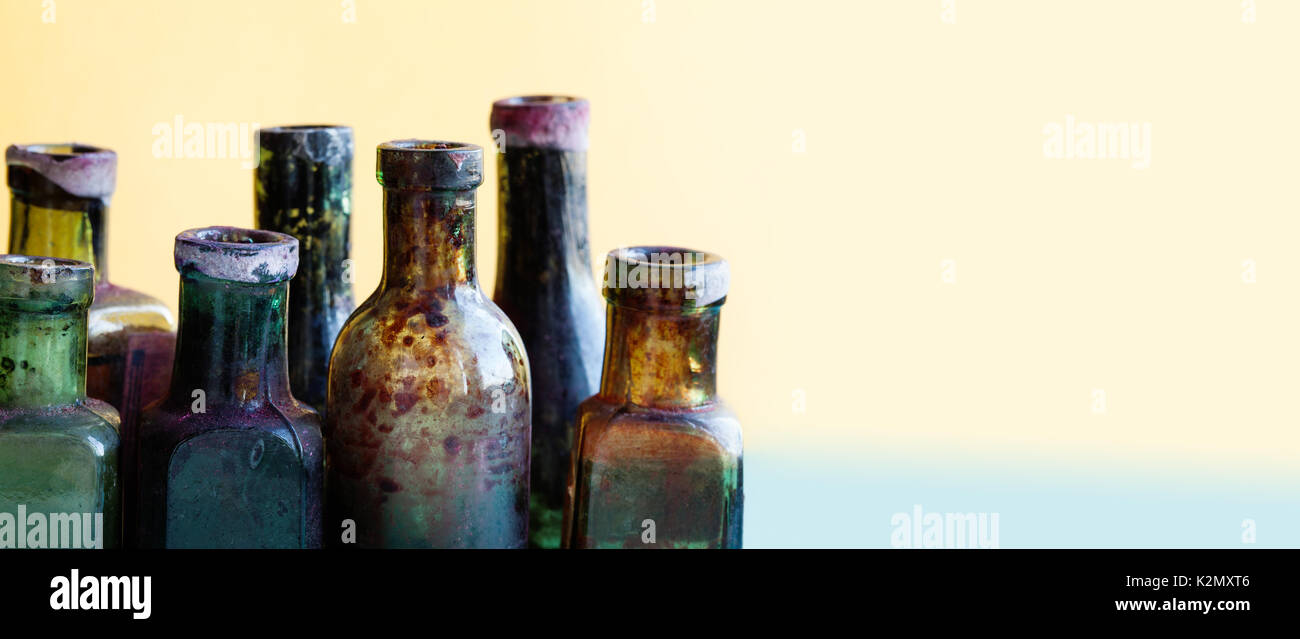 Ancient bottle macro view. Colorful dirty vintage design glass flacon set. Soft background, shallow depth of field. Copy text - Stock Image