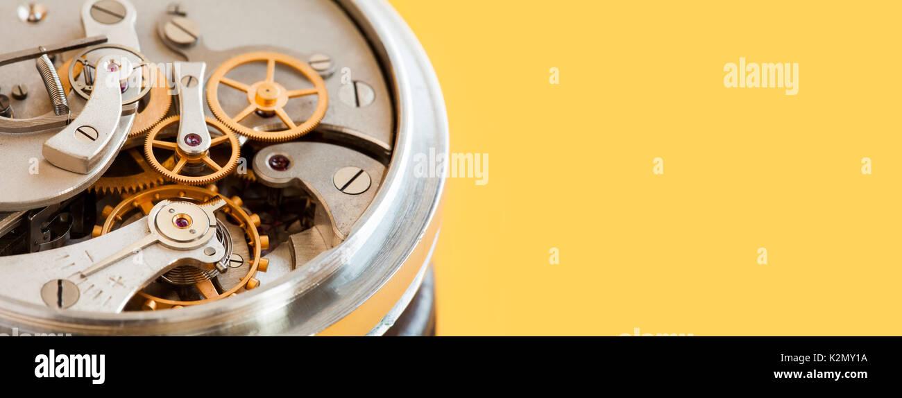 Vintage stopwatch chronometer mechanism macro view, yellow background. Selective focus photo. Copy space - Stock Image