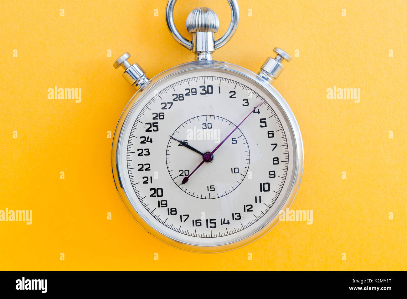 Retro style stopwatch chronometer on yellow paper textured background. Sport competition time management concept. Macro view, soft focus. - Stock Image