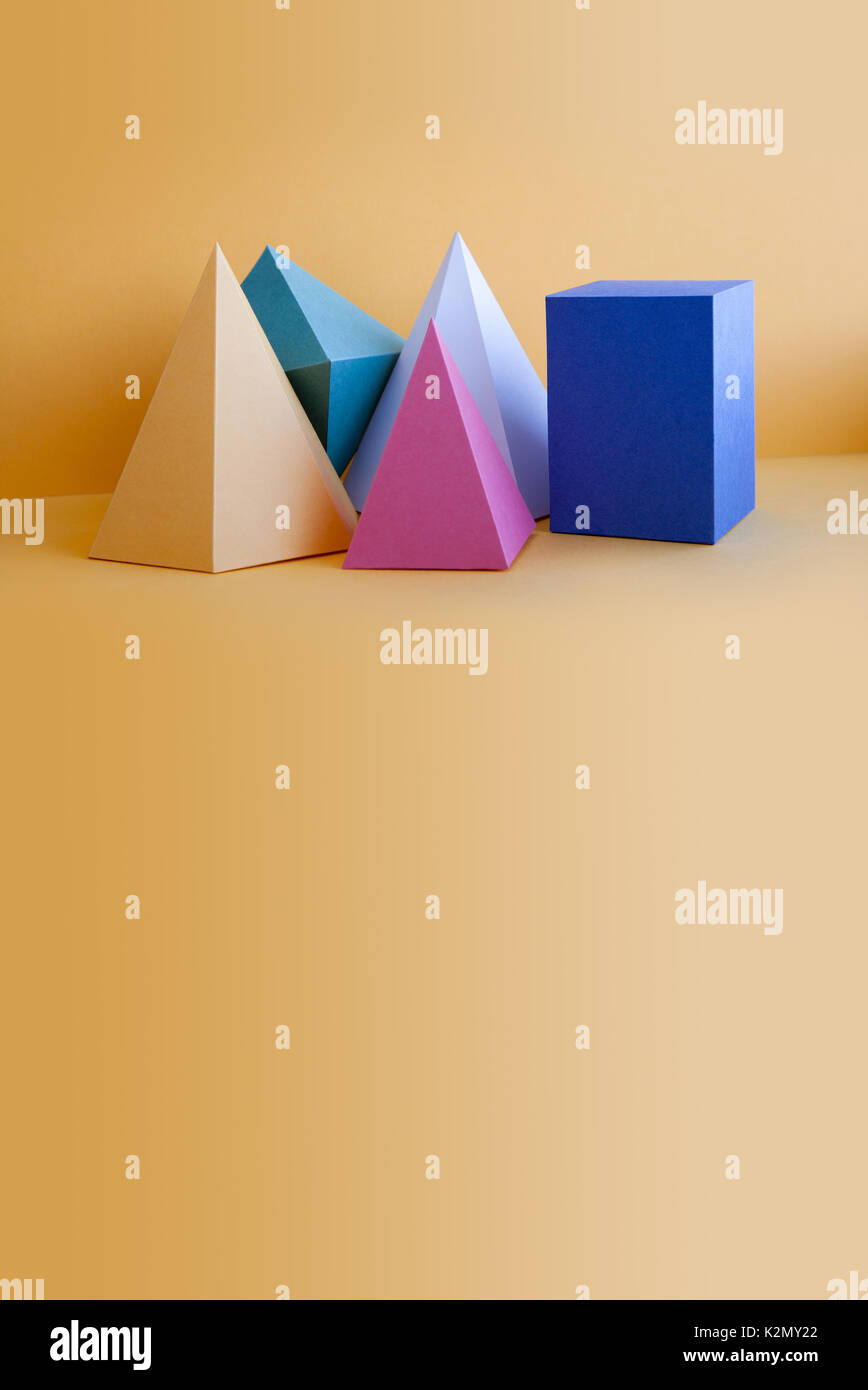 Colorful solid figures still life background. Three-dimensional prism pyramid rectangular cube objects on orange. Stock Photo