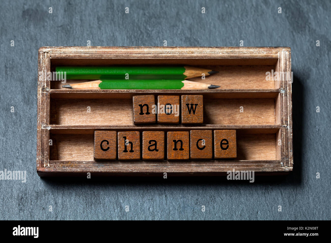 New chance phrase. Motivation and positive expectations concept. Vintage box, wooden cubes with old style letters, green pencils. Gray stone textured background. Close-up, up view, soft focus - Stock Image