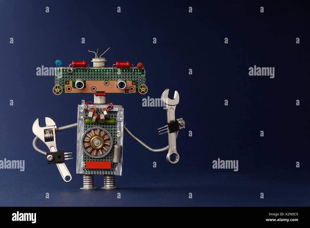 Hand wrench adjustable spanner robot handyman on dark blue paper background. Cute robotic toy made of electronic circuits, chip capacitors vintage resistors - Stock Image
