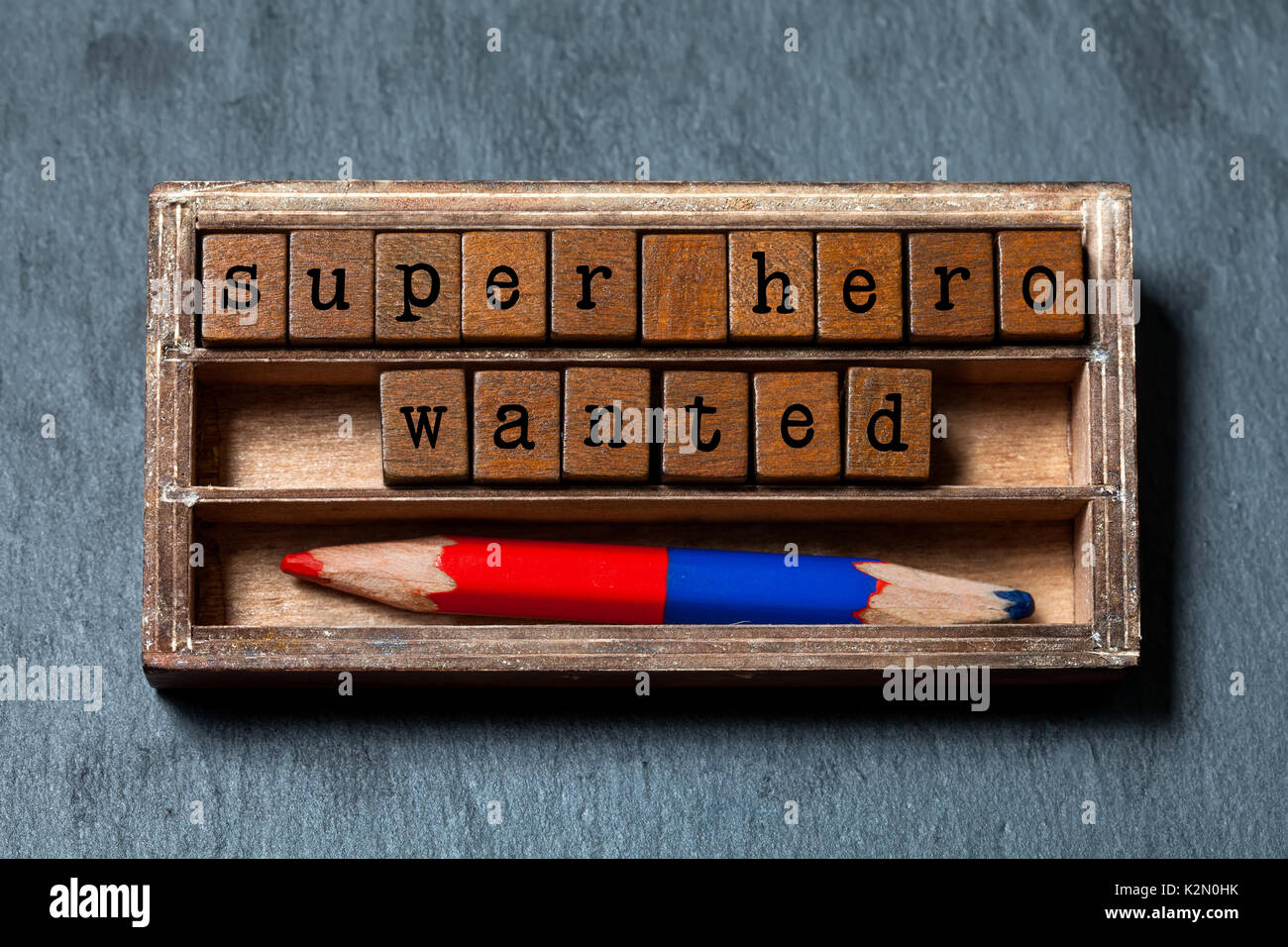 Super hero wanted phrase. Recruiting and personal searching concept quote. Vintage box, wooden cubes with old style letters, red blue pencil. Gray textured background. Close-up, up view, soft focus - Stock Image