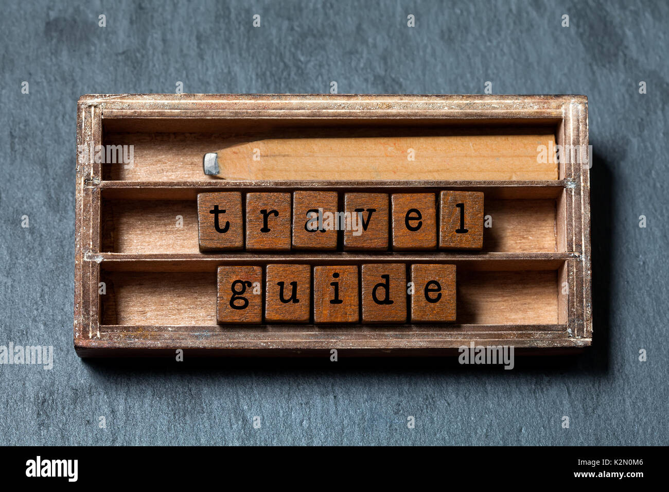 Travel guide concept. Vintage box, wooden cubes phrase with old style letters, retro pencil. Gray stone textured background. Close-up, up view, soft focus. - Stock Image