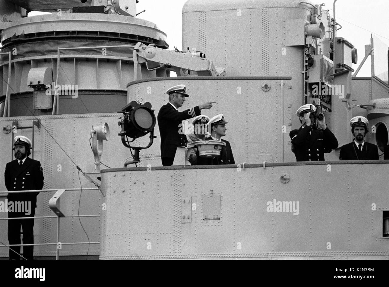 AJAXNETPHOTO. - 16TH AUGUST, 1979. PLYMOUTH, ENGLAND. - FASTNET END - CAPTAIN SCHMIDT (POINTING), C/O OF THE DUTCH NAVAL FRIGATE OVERIJSSEL WHICH RESCUED SURVIVORS OF THE STORM BATTERED 605 MILE OCEAN RACE, DOCKING THE SHIP ON ARRIVAL  AT DEVONPORT.  PHOTO:JONATHAN EASTLAND/AJAX. REF:791608_1_1 - Stock Image