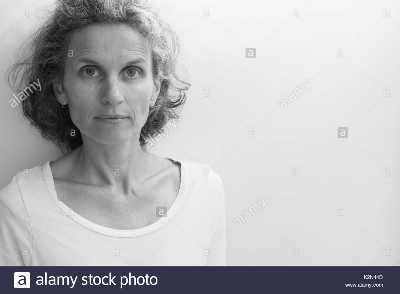 Portrait of natural looking middle aged woman against neutral background with copy space to right (black and white, selective focus) - Stock Image