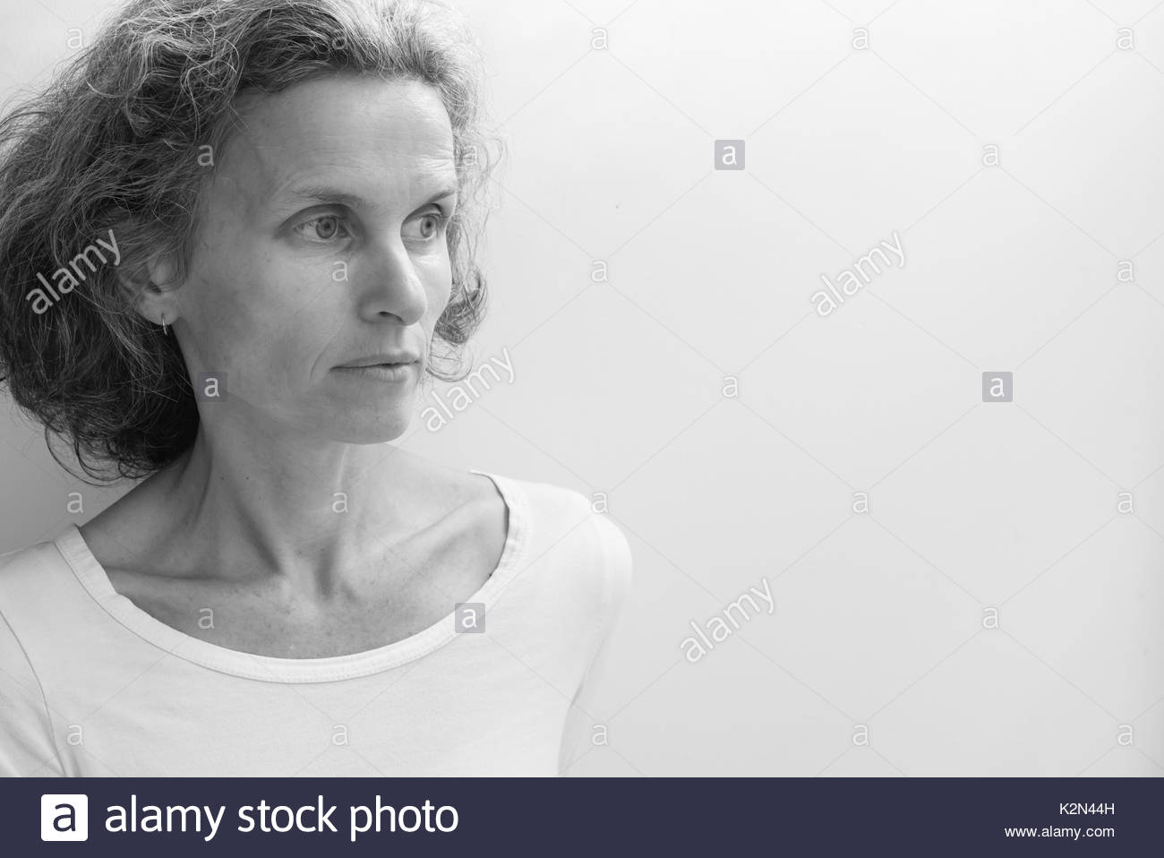 Profile view of natural looking middle aged woman in white top against neutral background with copy space to right (black and white, selective focus) - Stock Image