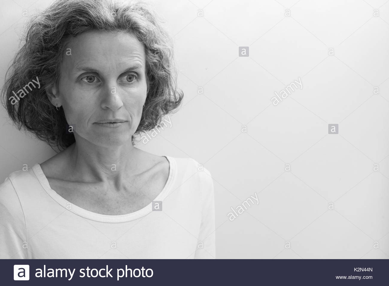 Natural looking middle aged woman in white top against neutral background with copy space to right (black and white, selective focus) - Stock Image