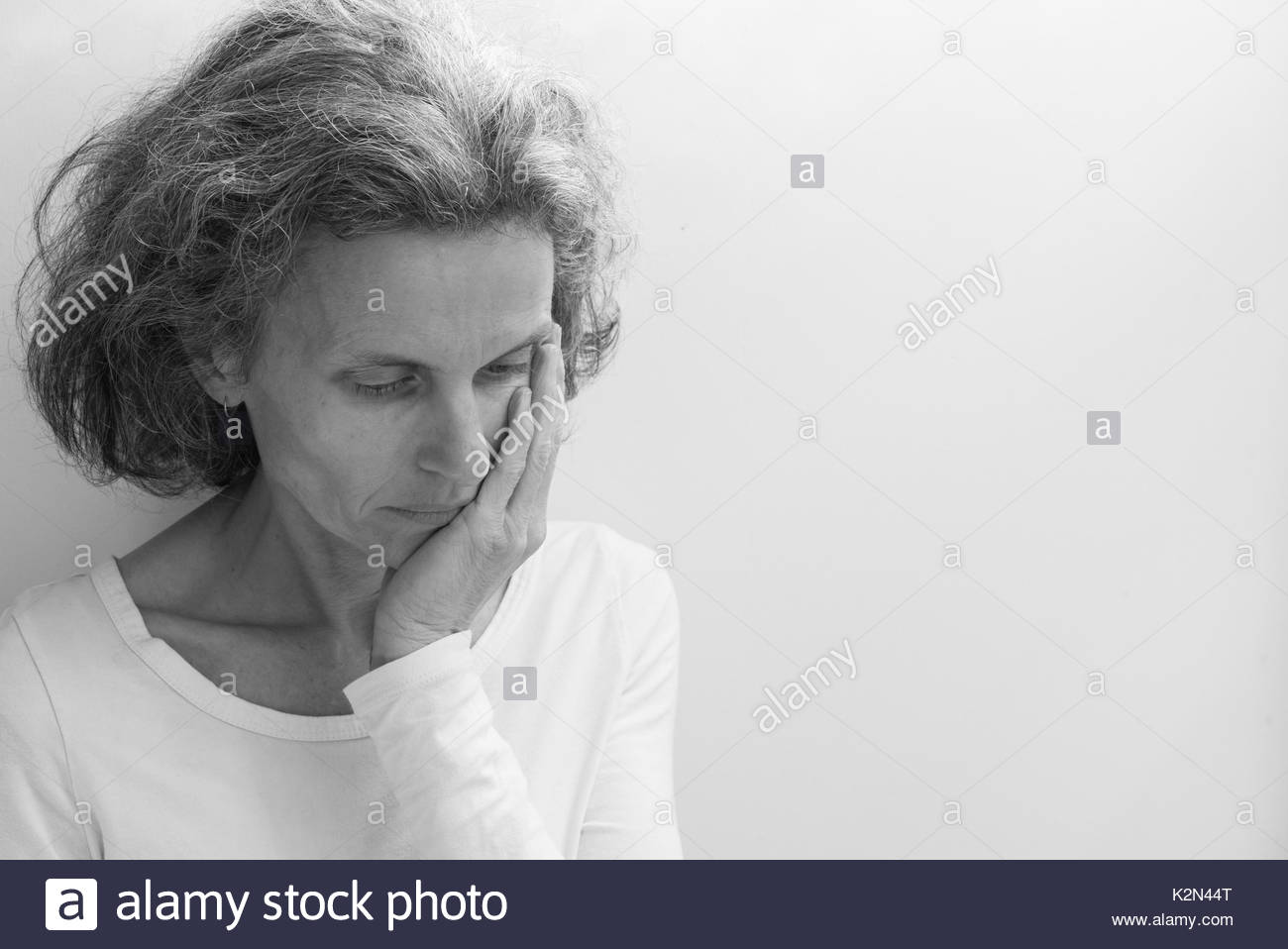 Middle aged woman in white top wiht hand on face against neutral background with copy space to right (black and white, selective focus) - Stock Image