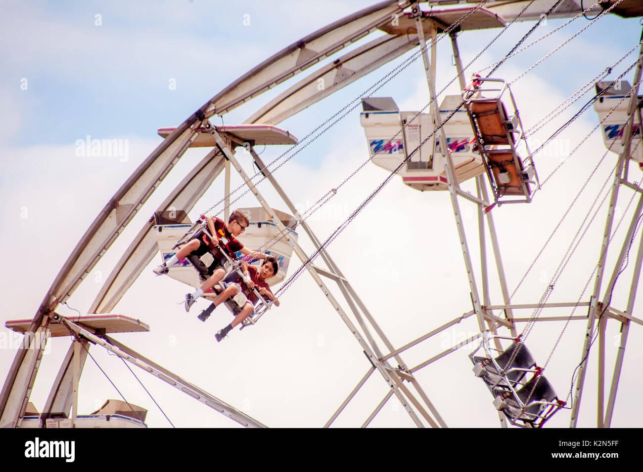 Boys on a 'Vertigo' ride are juxtaposed with a Ferris wheel at a Costa Mesa, CA, amusement park. - Stock Image