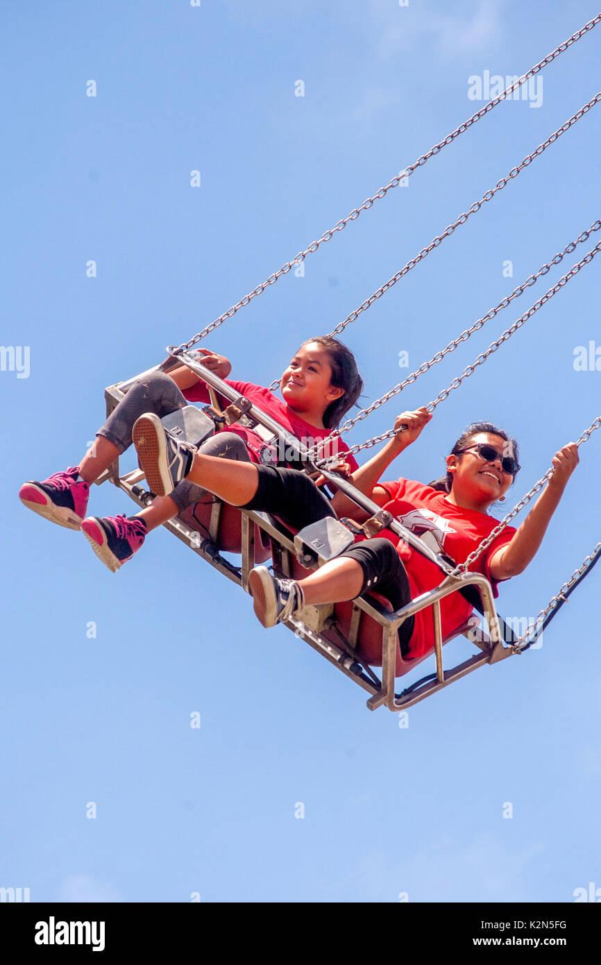 Hispanic teen girls enjoy a 'Vertigo' ride at a Costa Mesa, CA, amusement park. - Stock Image