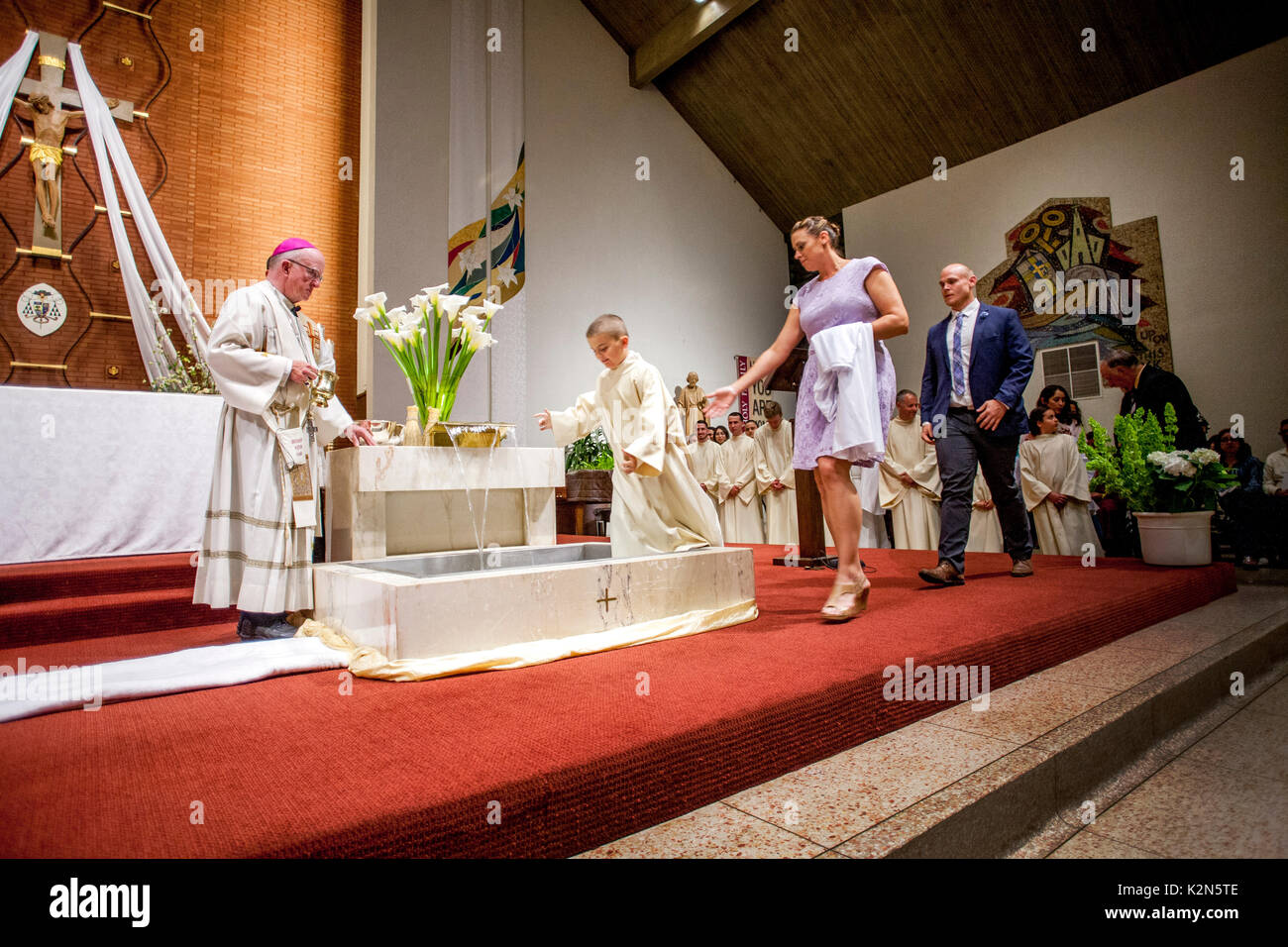 Accompanied by his parents and sponsors, a boy wearing a baptism robe enters the font at a Catholic cathedral in Orange, CA. Note bishop at left. Note other baptism candidates in background. - Stock Image