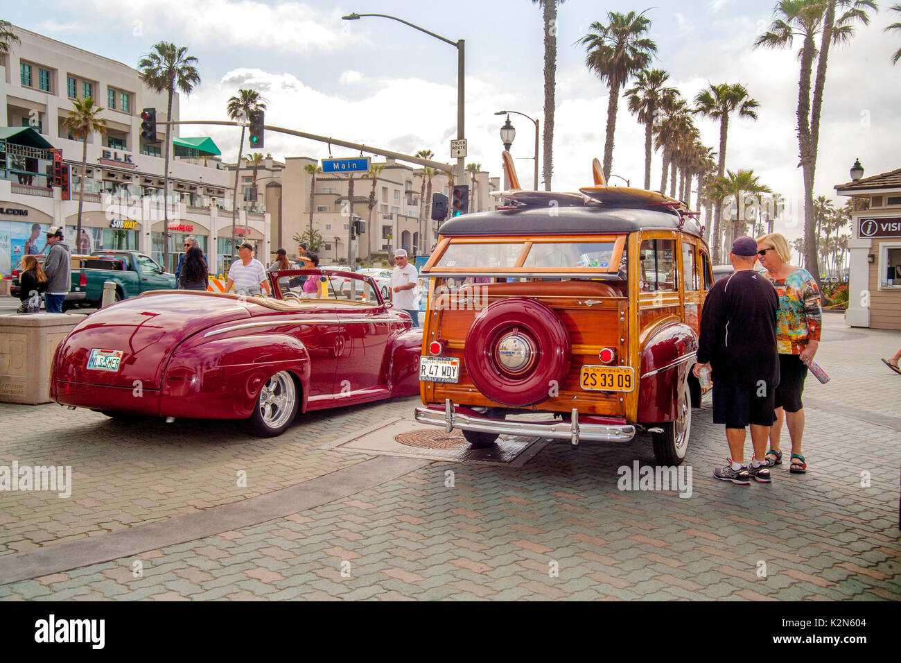 A 1947 Ford convertible and 1947 Ford Super Deluxe 'woodie' station wagon are on display at a classic car show in downtown Huntington Beach, CA.  Note  surfboards on roof, antique license plate and palm trees. - Stock Image