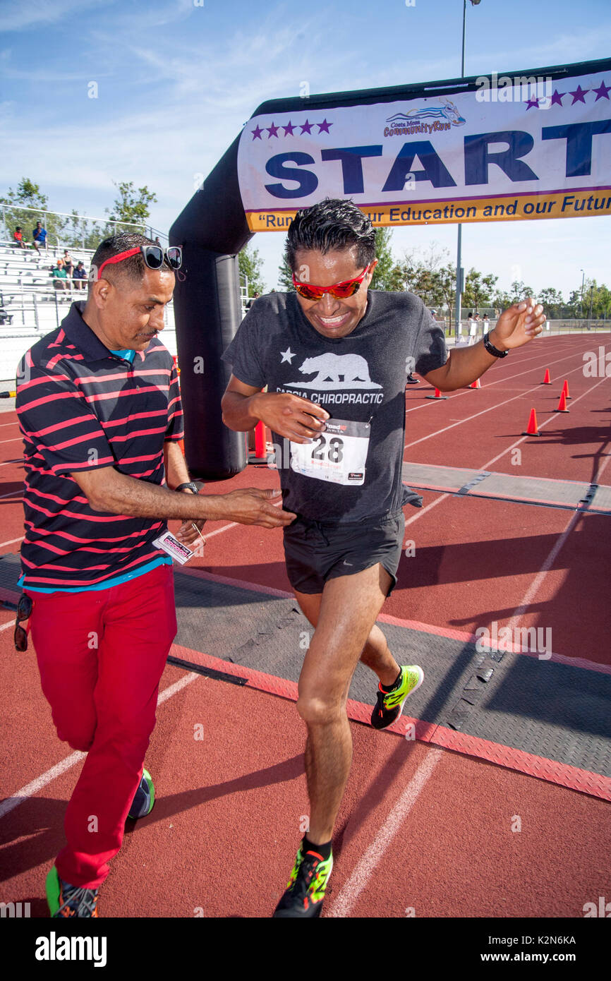 The Hispanic winner of a foot race crosses the finish line at a track meet in Costa Mesa, CA, as his father reaches offers congratulations. - Stock Image