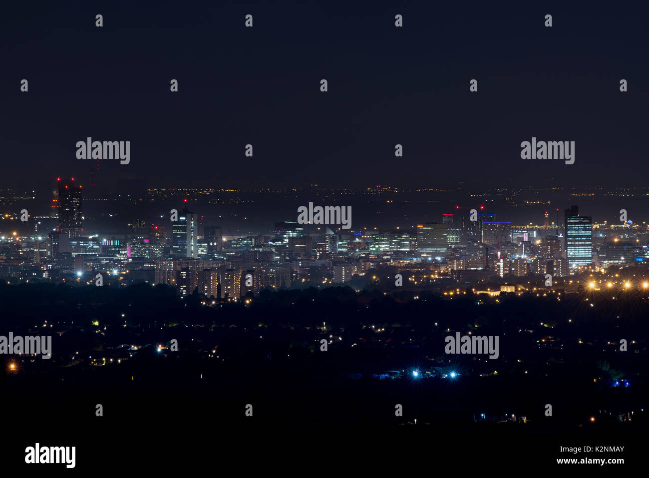 A view of Manchester City Centre taken at night from the vantage point of Hartshead Pike, Mossley, in Saddleworth, UK - Stock Image
