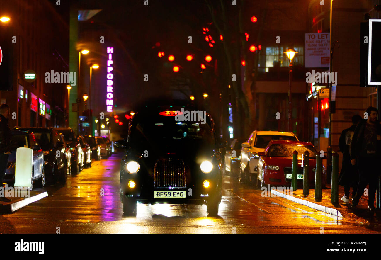Bustling city centre street scene after rain with wet roads and reflections, many coloured lights and in Chinatown - Stock Image