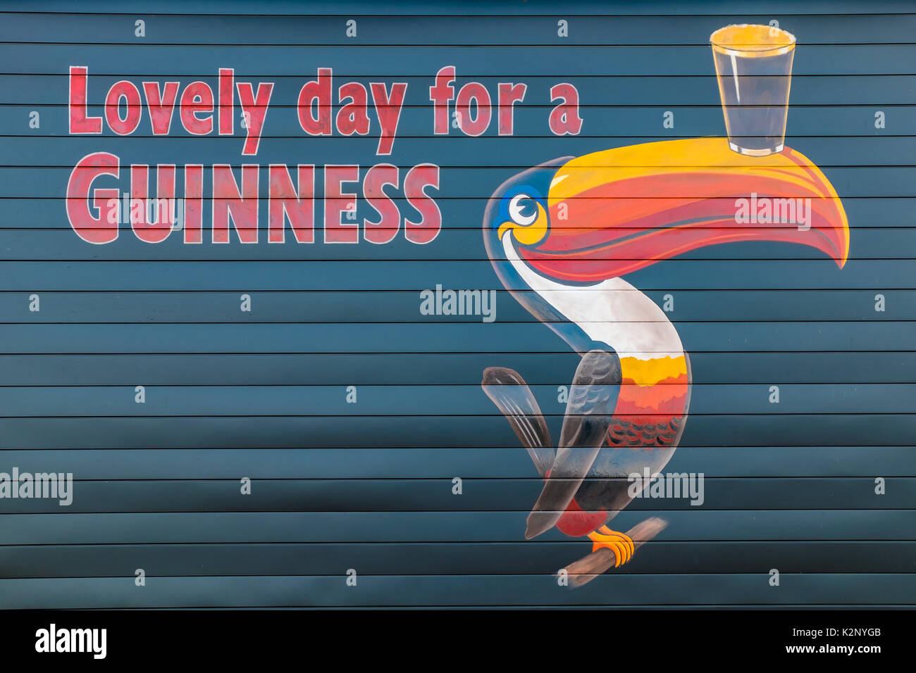 Painted Guinness sign featuring a slogan and a toucan balancing a beer on a wall in Orillia Ontario Canada. - Stock Image