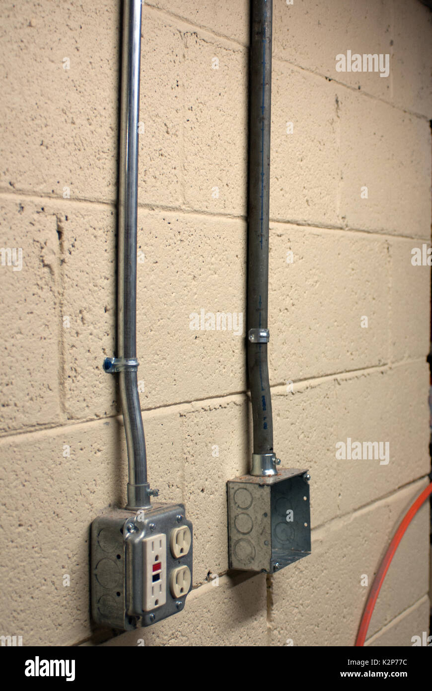 electricity outlet boxes with conduit on painted cinderblock wall rh alamy com