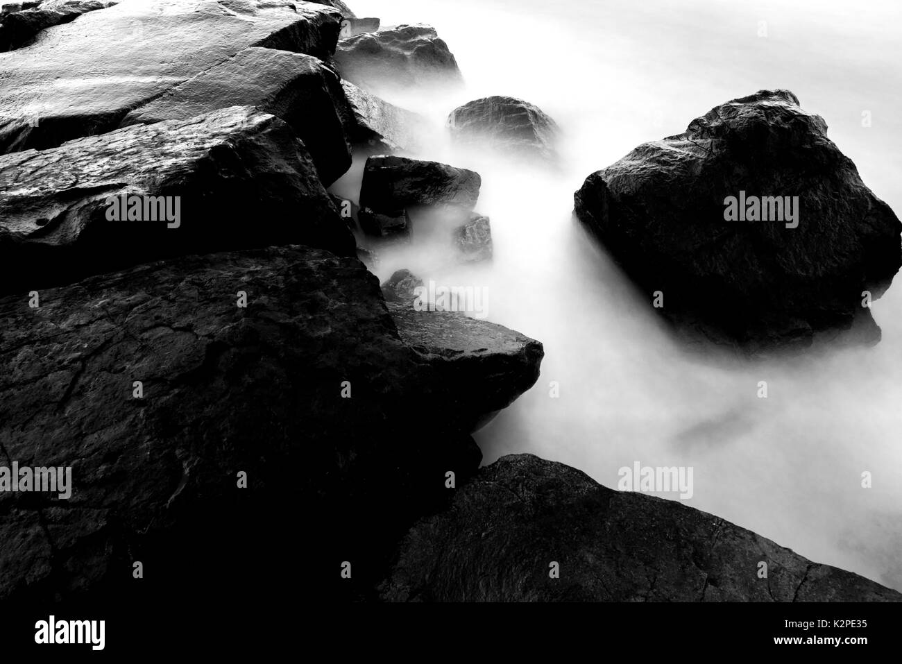 Black and white long exposure water and stones background in cool colors - Stock Image