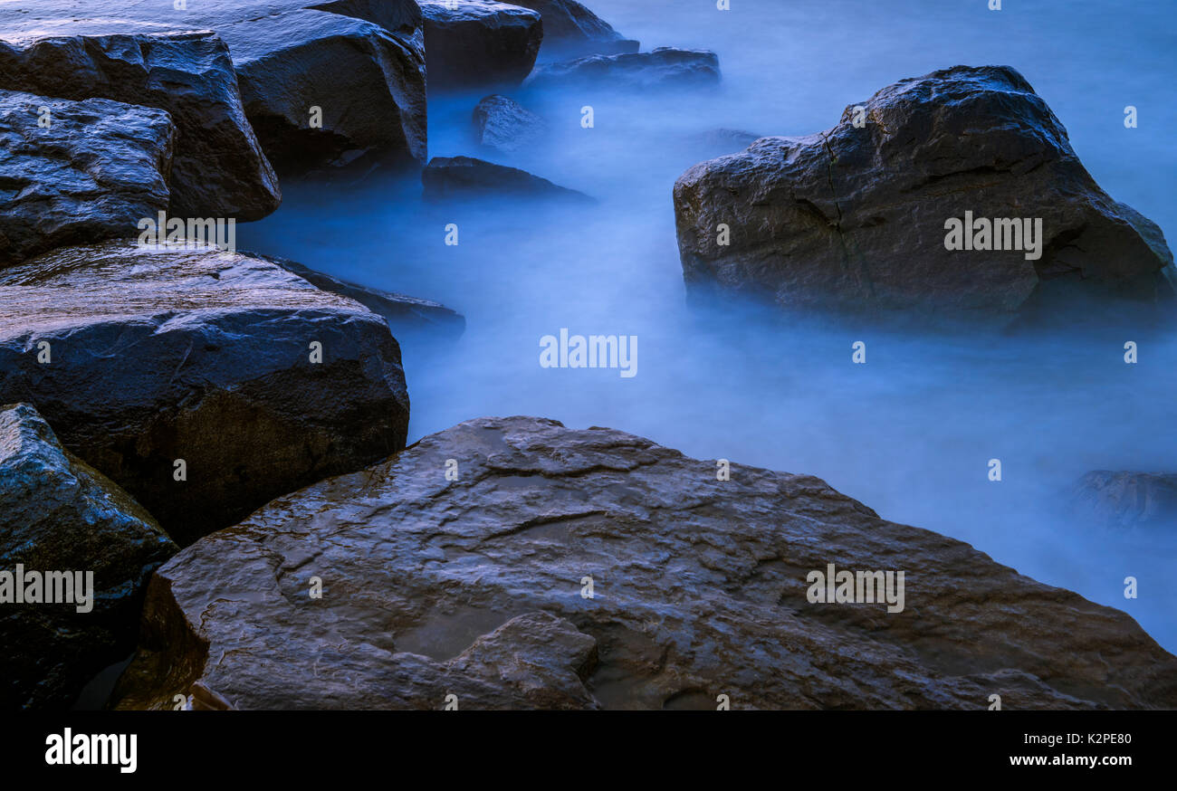 Beautiful long exposure water and stones background in cool colors - Stock Image