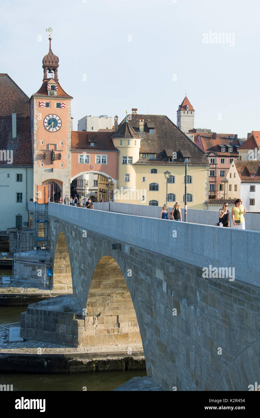 Crossing the Danube (Donau) on a restored section of the Stone Bridge or Steinerne Bruecke at Regensburg, Bavaria, Germany - Stock Image