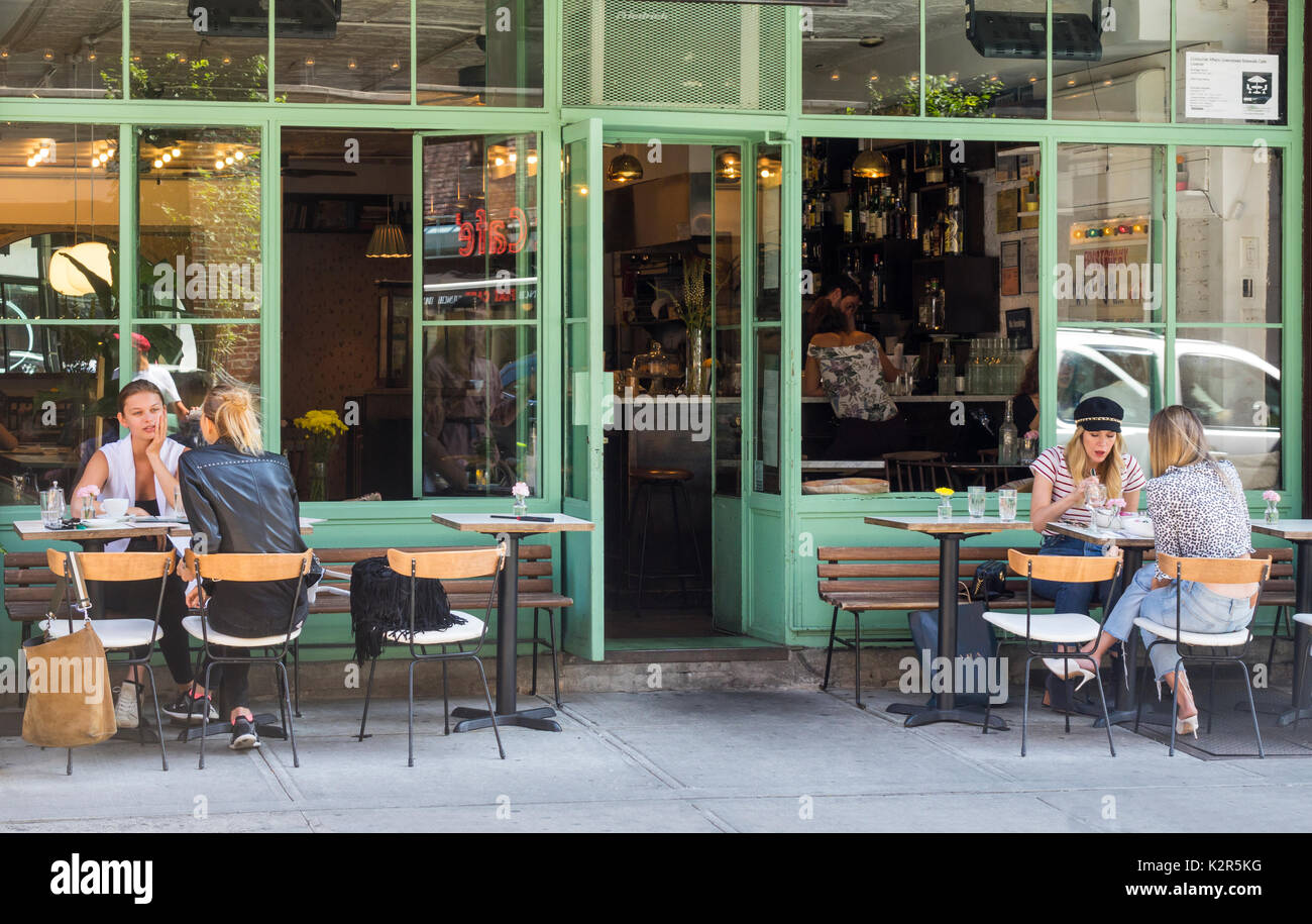 Four attractive young women having an alfresco lunch at a Nolita bistro n Lower Manhattan - Stock Image