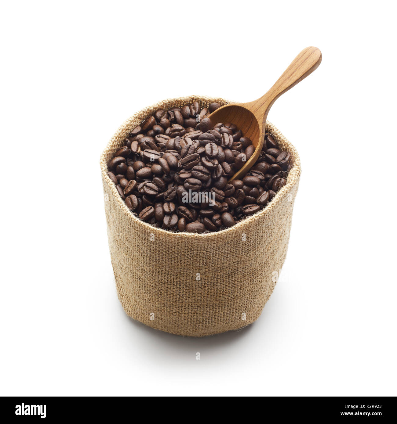 Coffee beans, burlap sack and wooden scoop isolated on white background - Stock Image