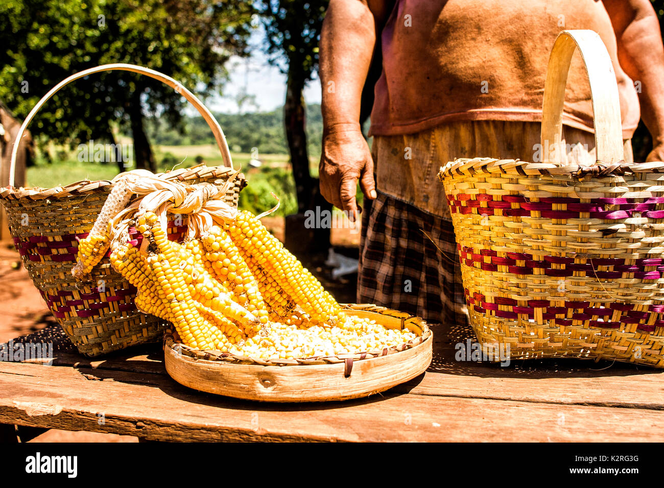 Member of Guarani ethnic group in Xapeco Indian Reserve and some examples of their handicraft work. Entre Rios, Santa Catarina, Brazil. - Stock Image