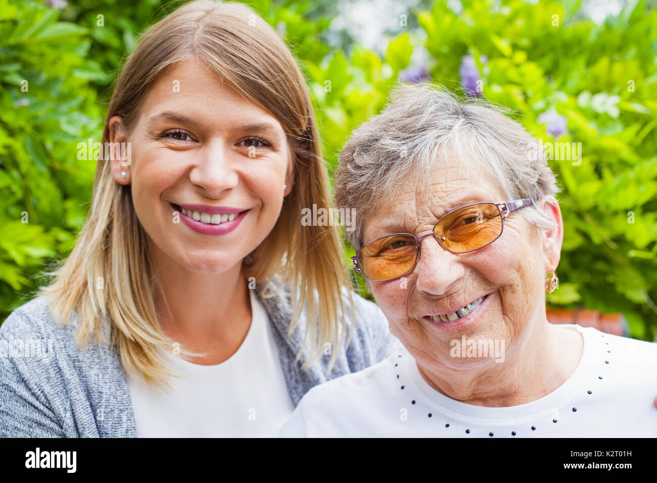 Portrait of elderly woman with damaged dental bridge smiling at the camera with her caretaker outdoor - Stock Image