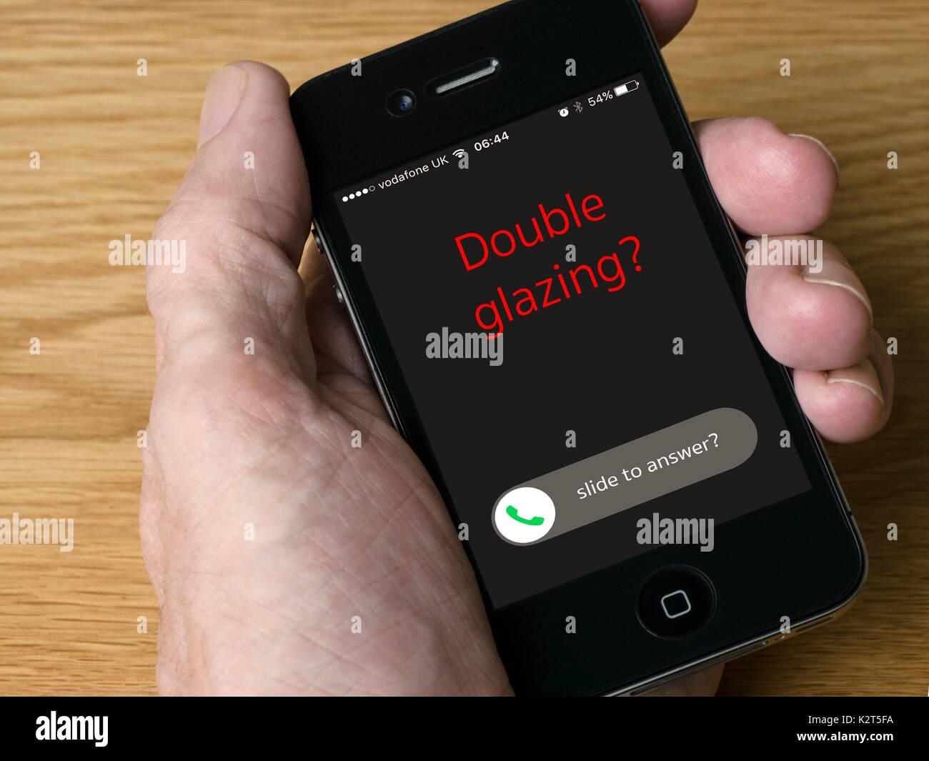 Concept image - Incoming double glazing salesman nuisance call on iPhone mobile phone display - Stock Image