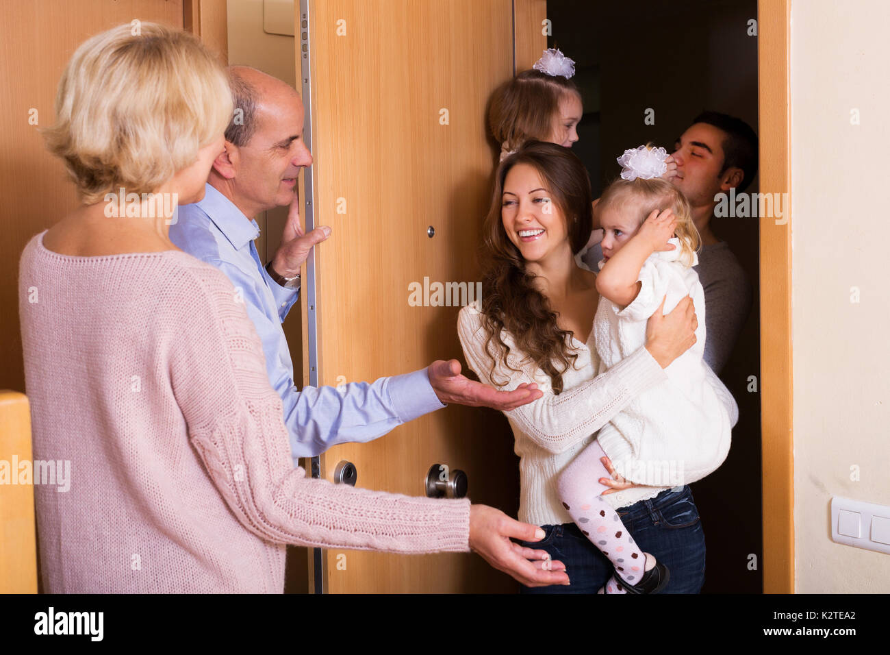 young family with two daughters visiting grand parents - Stock Image