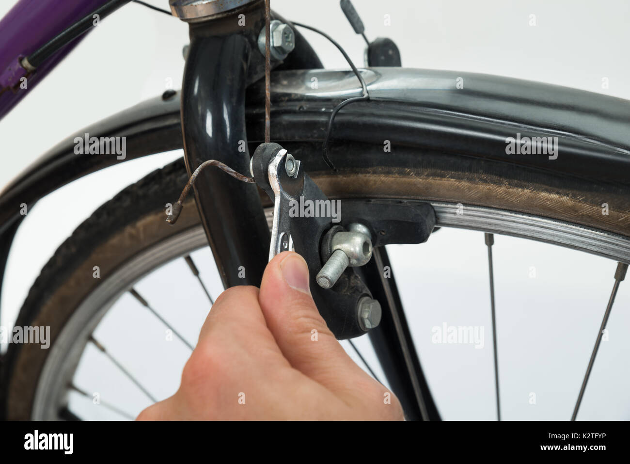 Close-up Of Person Hands Tightening Bolt Of Bicycle Tire With Wrench - Stock Image