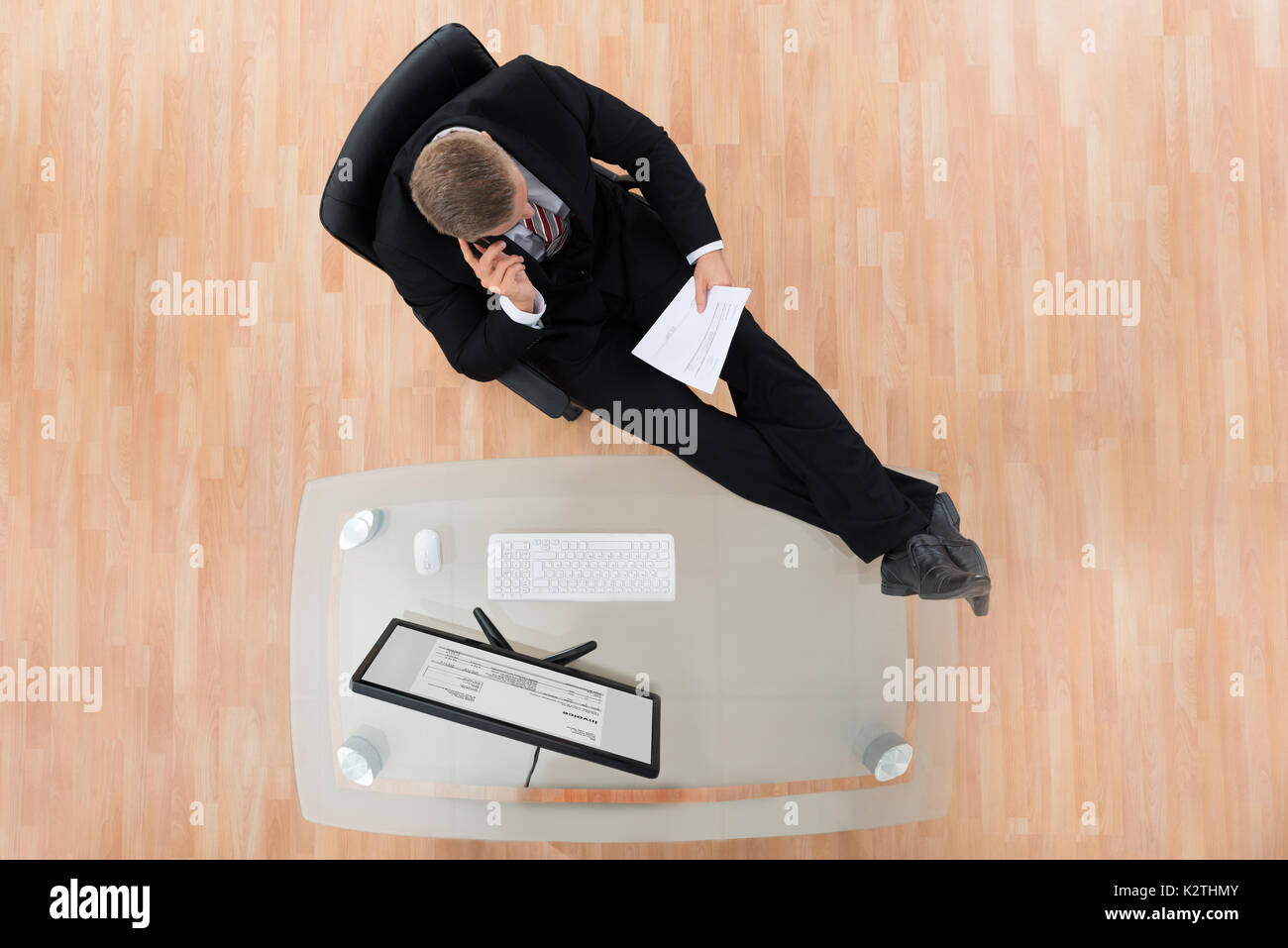 Businessman Reading Document While Sitting At The Desk In Office - Stock Image