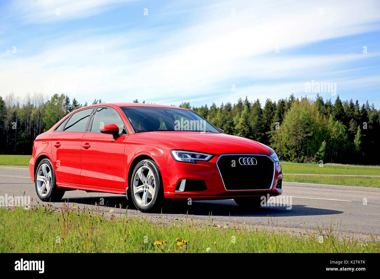KAARINA, FINLAND - JUNE 3, 2017: New beautiful Tango red Audi A3 Sedan Business Sport 2017 parked on side of highway on a clear day of early summer. - Stock Image