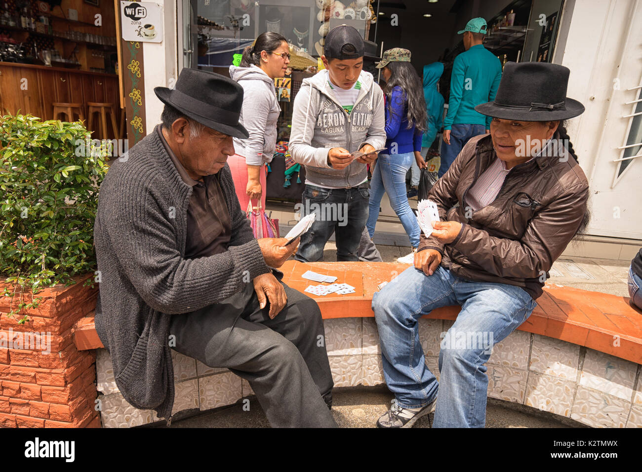 May 6, 2017 Otavalo, Ecuador: indigenous quechua men playing cards on the street in the Saturday market - Stock Image
