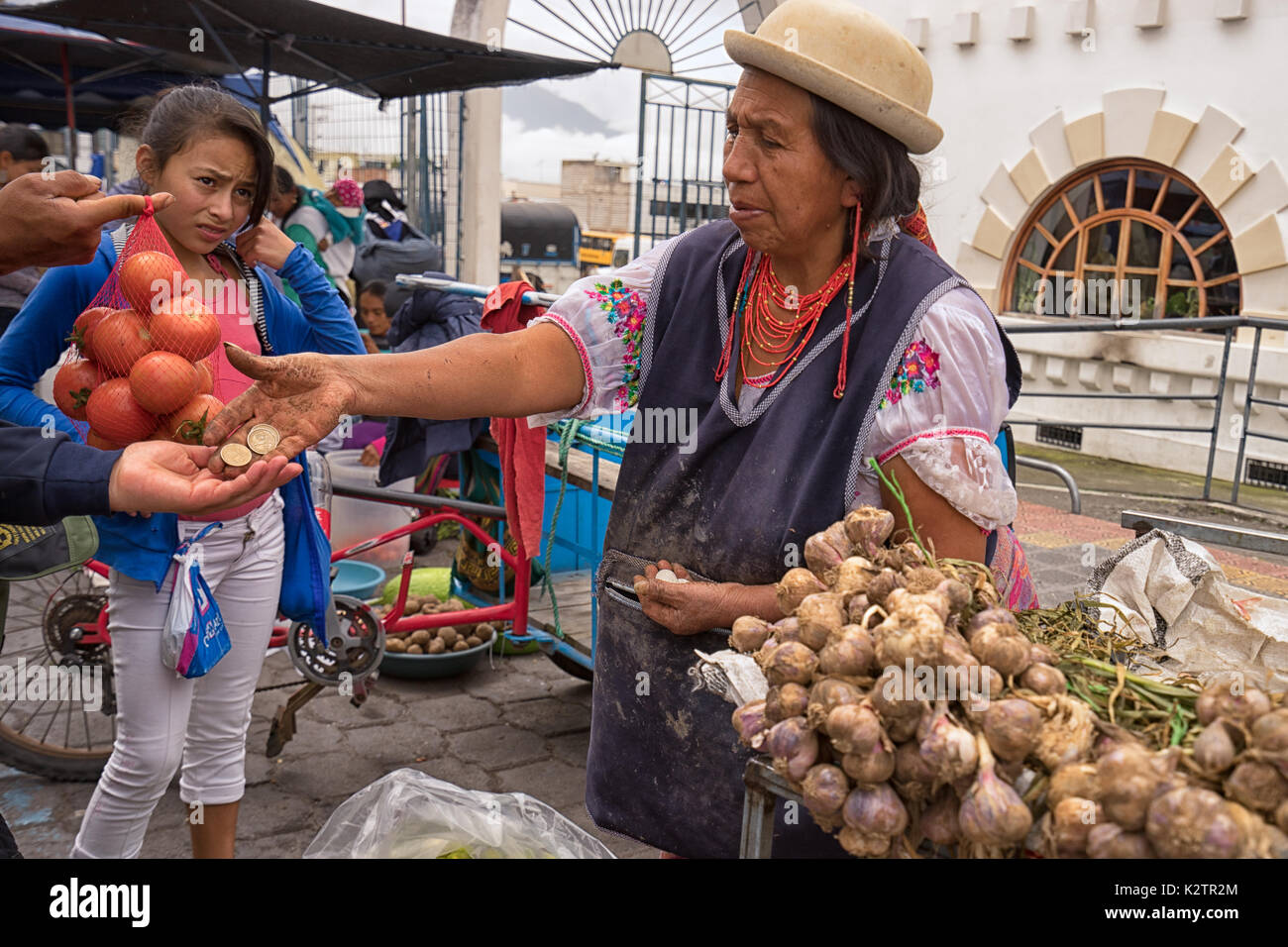 May 6, 2017 Otavalo, Ecuador: produce vendor in the Saturday market giving change to costumer - Stock Image