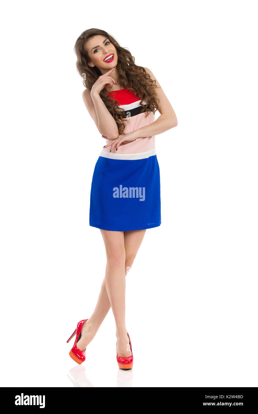 Beautiful young woman in colorful mini dress and red high heels is standing with legs crossed, smiling, and looking at camera. Front view. Full length - Stock Image