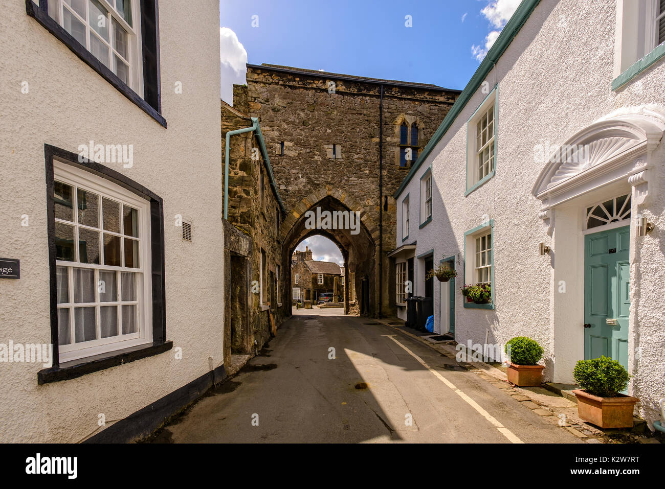Lovely old street in Cartmel village with view through stone arch into main square - Stock Image