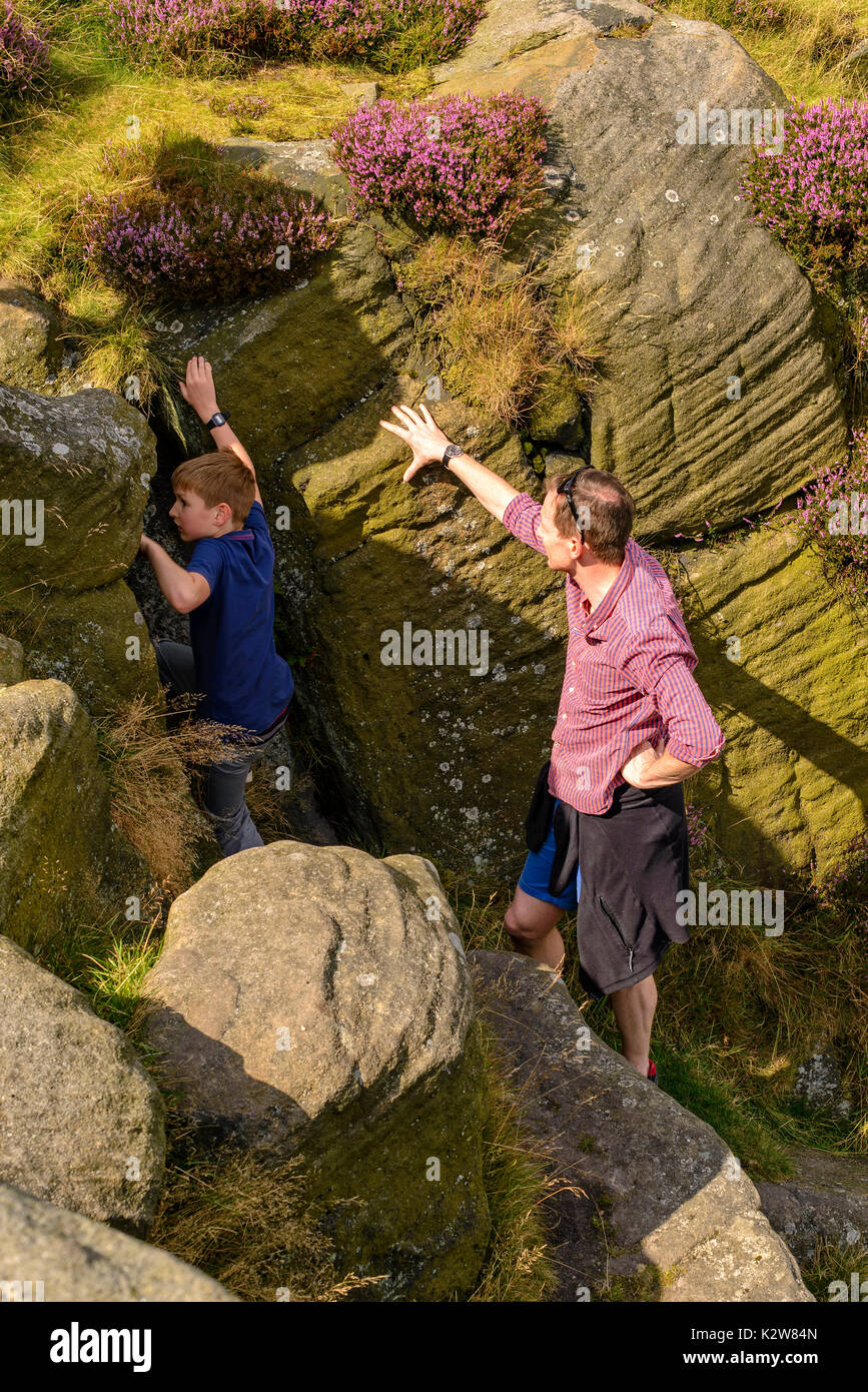 Family fun scambling up rocks on the Yorkshire moors - Stock Image