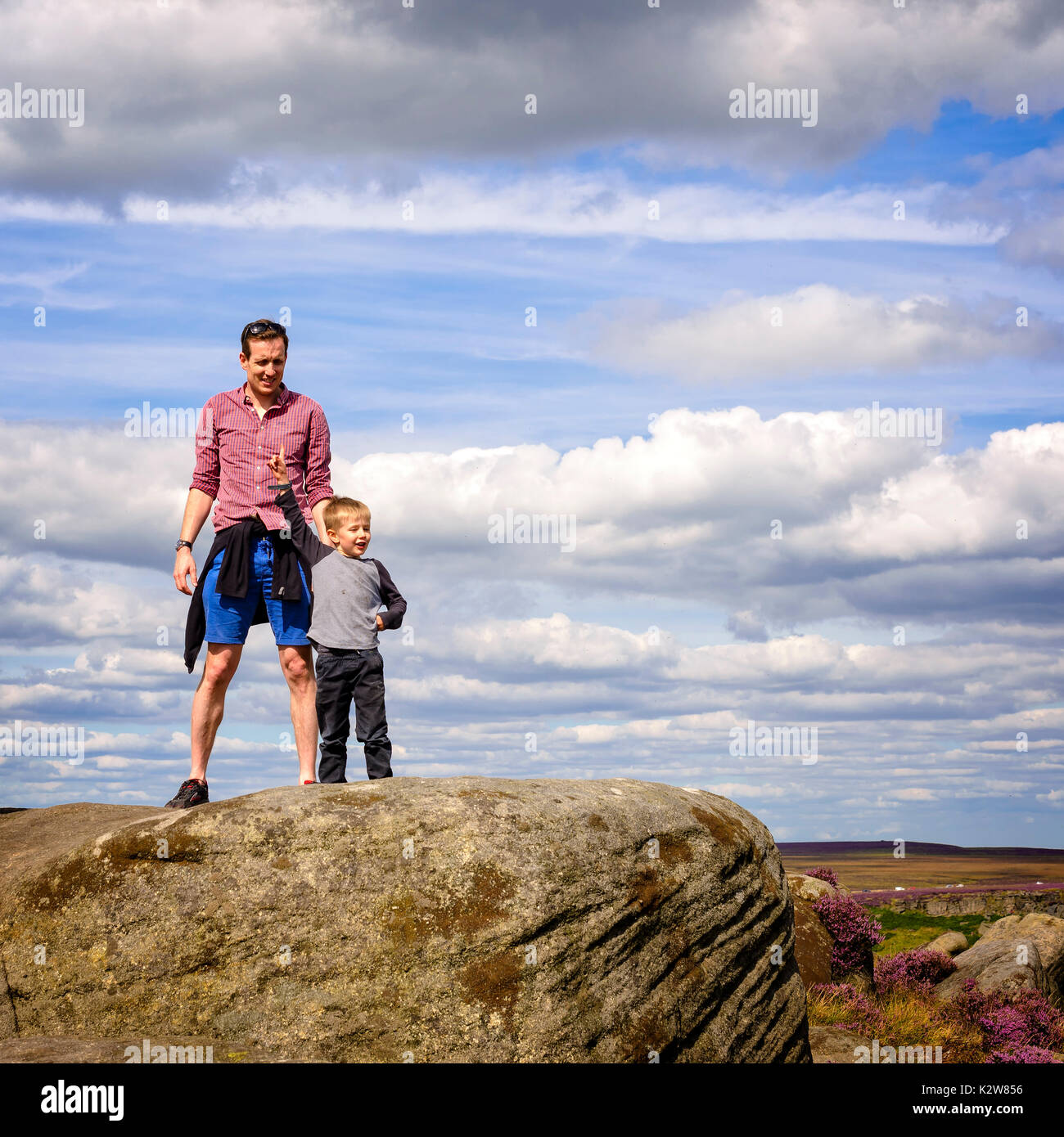 Father and son enjoying the views after scrambling up onto the rocks on moors just outside Sheffield. - Stock Image