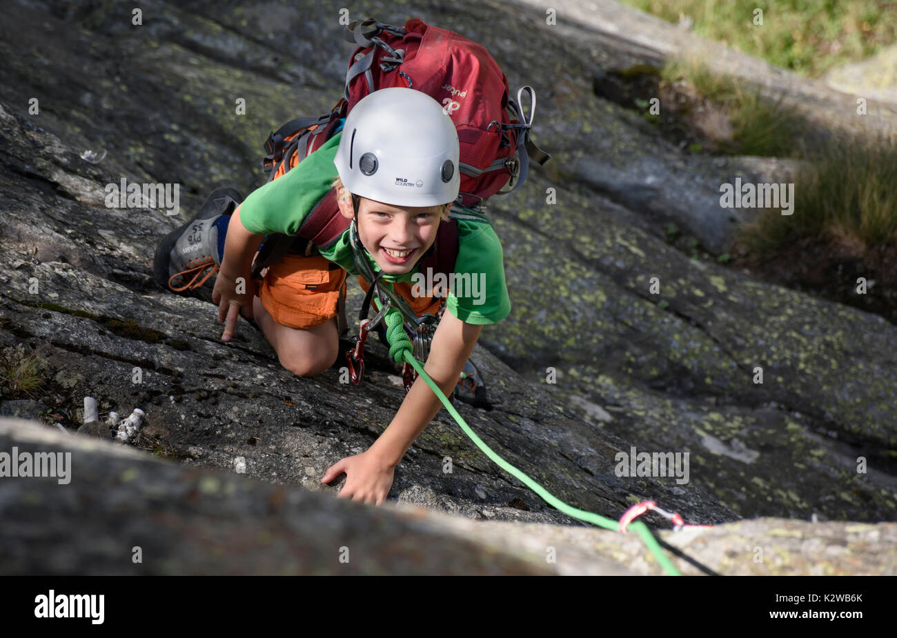 A young boy rock climbing on the slabs at the Burghutte in Fieschertal Stock Photo